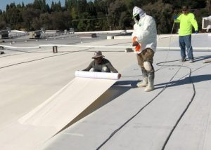 workers roll out fabric on an acrylic roof